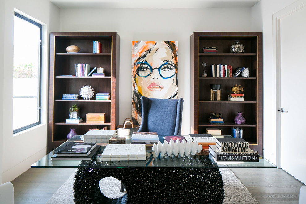 Example of a mid-sized trendy freestanding desk light wood floor study room design in Orange County with white walls