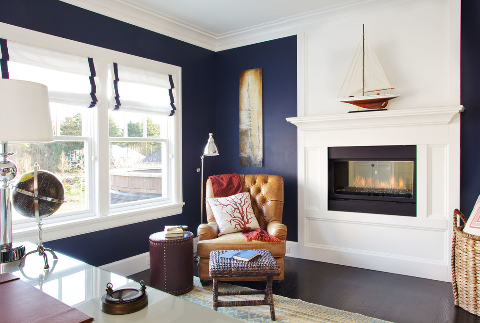 Large coastal freestanding desk dark wood floor home office photo in Portland with blue walls, a two-sided fireplace and a wood fireplace surround