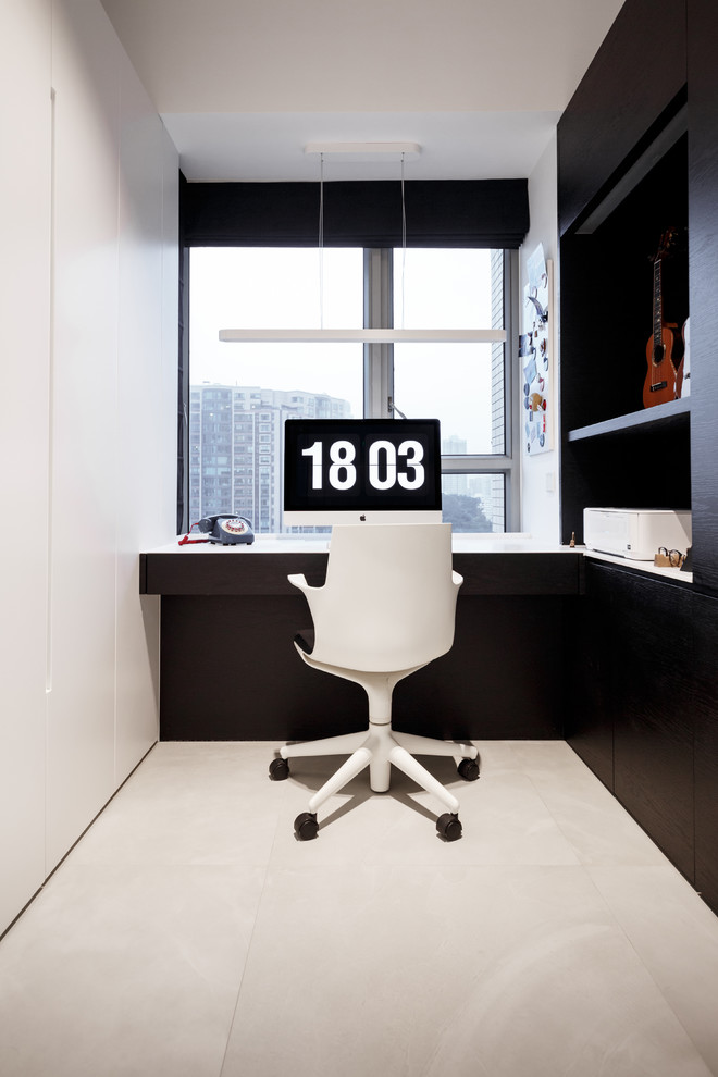 Inspiration for a small modern built-in desk concrete floor study room remodel in Hong Kong with white walls