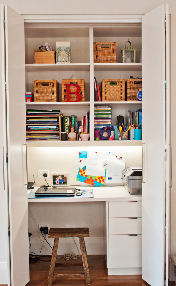 Inspiration for a small contemporary built-in desk medium tone wood floor home office remodel in Melbourne with white walls
