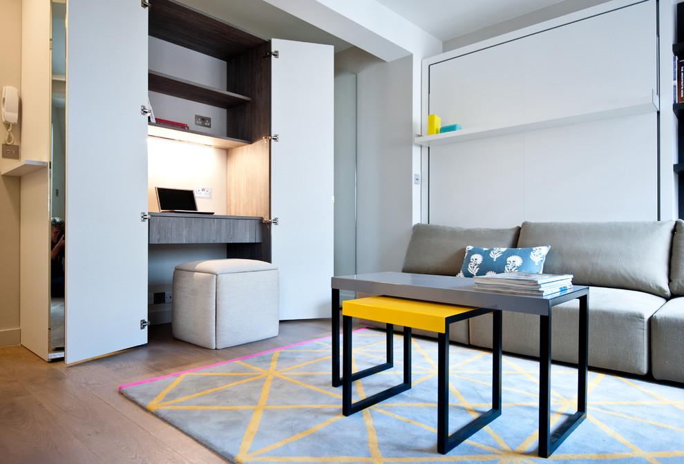 Study room - small contemporary built-in desk medium tone wood floor study room idea in London with gray walls