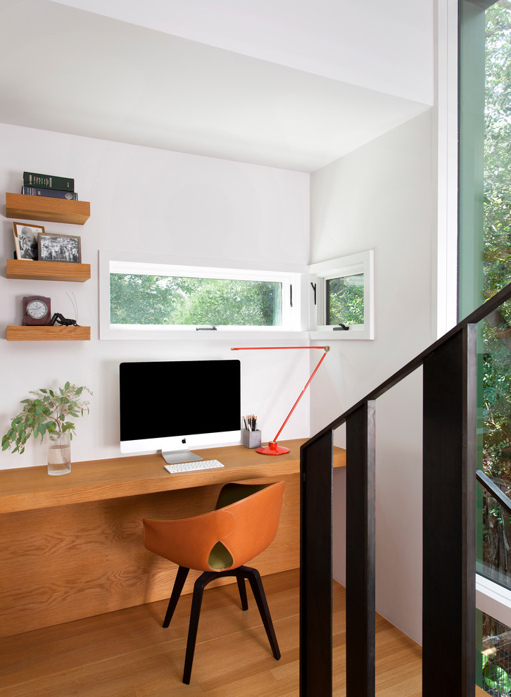 Home office - small contemporary built-in desk medium tone wood floor and brown floor home office idea in Austin with no fireplace and white walls