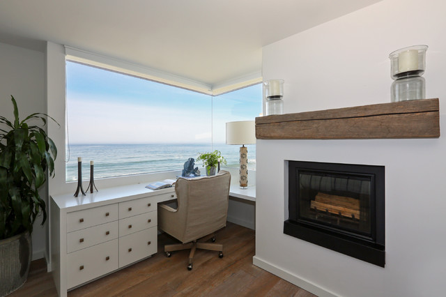 Coastal built-in desk dark wood floor home office photo in Santa Barbara with white walls and a standard fireplace