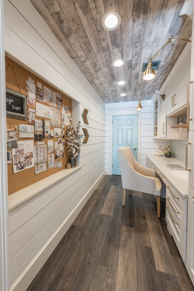 Example of a small country built-in desk vinyl floor and brown floor study room design in Other with white walls