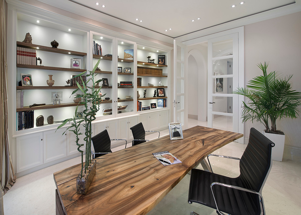 Example of a tuscan freestanding desk home office design in Miami with gray walls