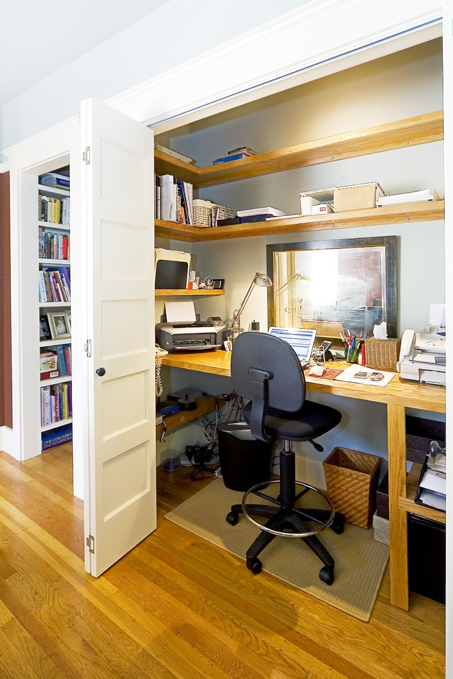 Elegant built-in desk medium tone wood floor home office photo in San Francisco with gray walls