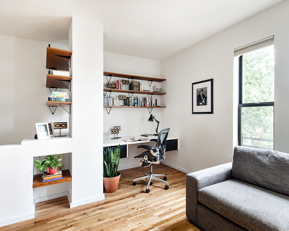 Study room - small scandinavian built-in desk light wood floor study room idea in New York with white walls and no fireplace