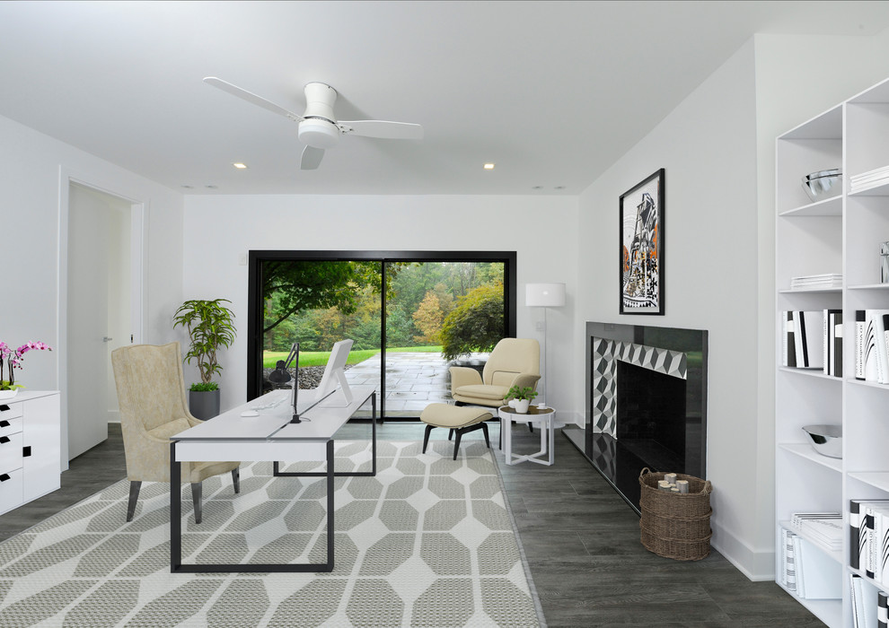 Example of a large trendy freestanding desk dark wood floor and gray floor home office design in New York with white walls, a standard fireplace and a tile fireplace