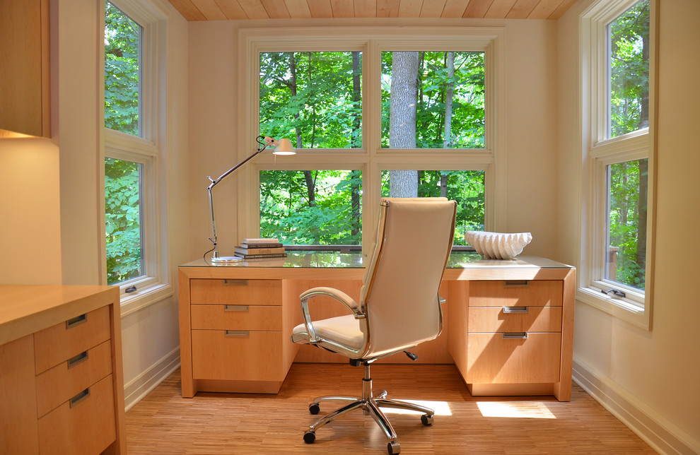 Trendy freestanding desk medium tone wood floor home office photo in Milwaukee with beige walls