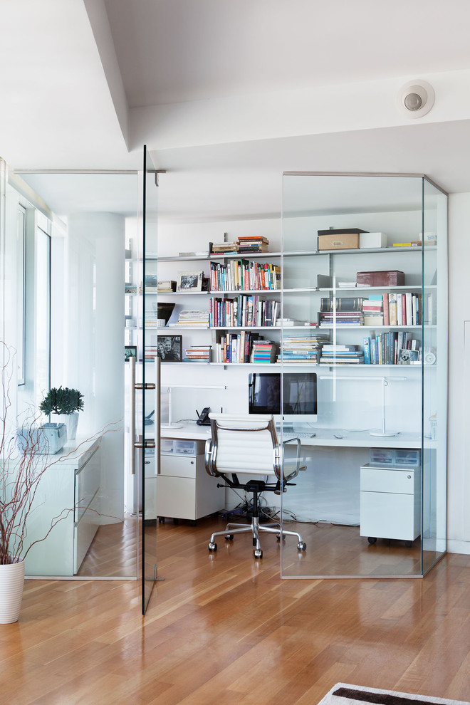 Trendy built-in desk medium tone wood floor home office photo in New York with white walls