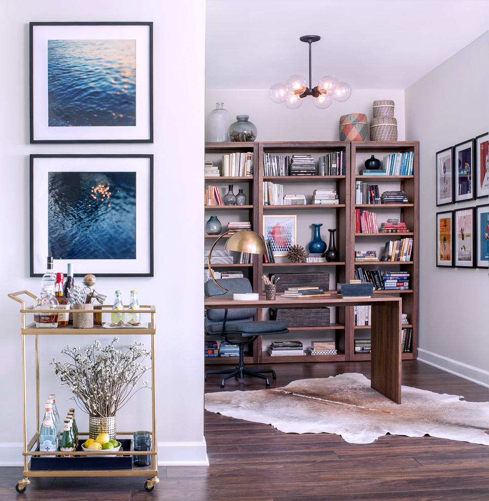 Example of a trendy freestanding desk medium tone wood floor study room design in Chicago with white walls