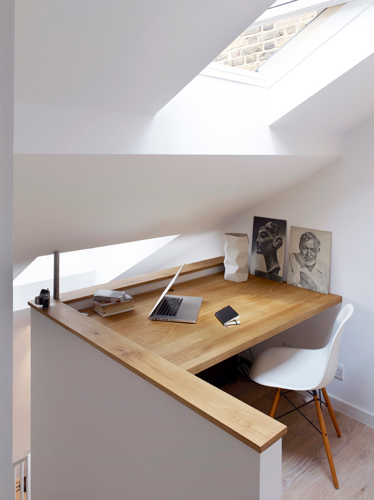 Small minimalist built-in desk light wood floor study room photo in London with white walls
