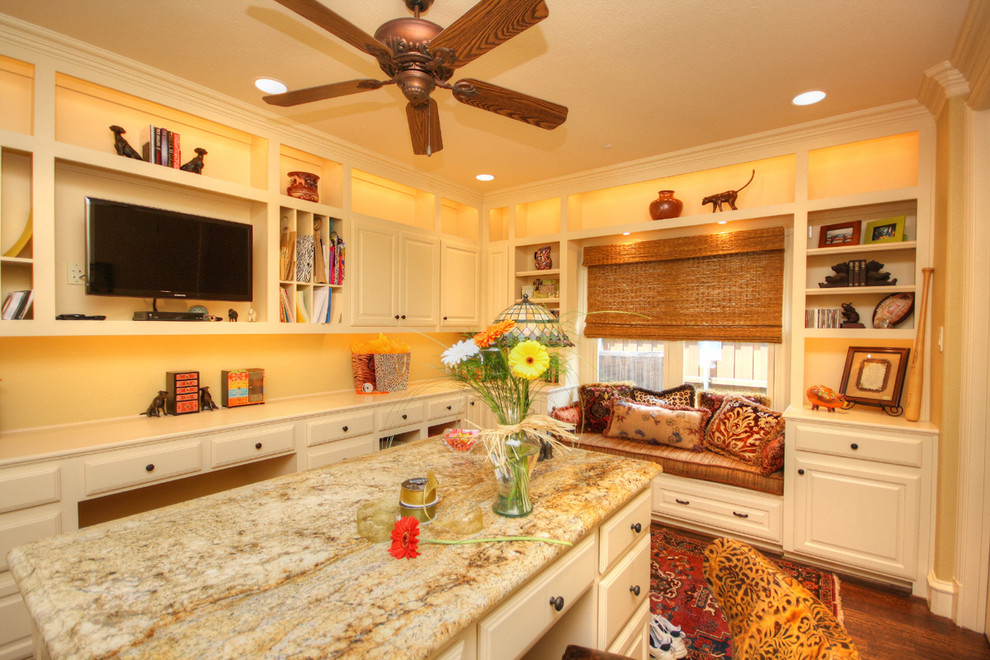 Example of a mid-sized classic built-in desk medium tone wood floor craft room design in Dallas with yellow walls