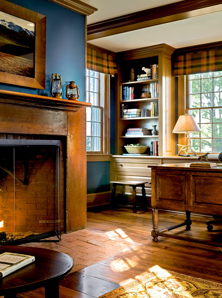 Inspiration for a timeless medium tone wood floor and brown floor home office remodel in New York with blue walls, a brick fireplace and a standard fireplace