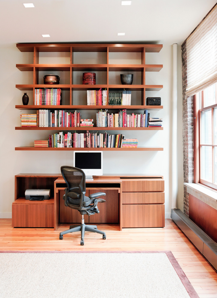 Example of a mid-sized trendy built-in desk light wood floor home office design in New York with white walls