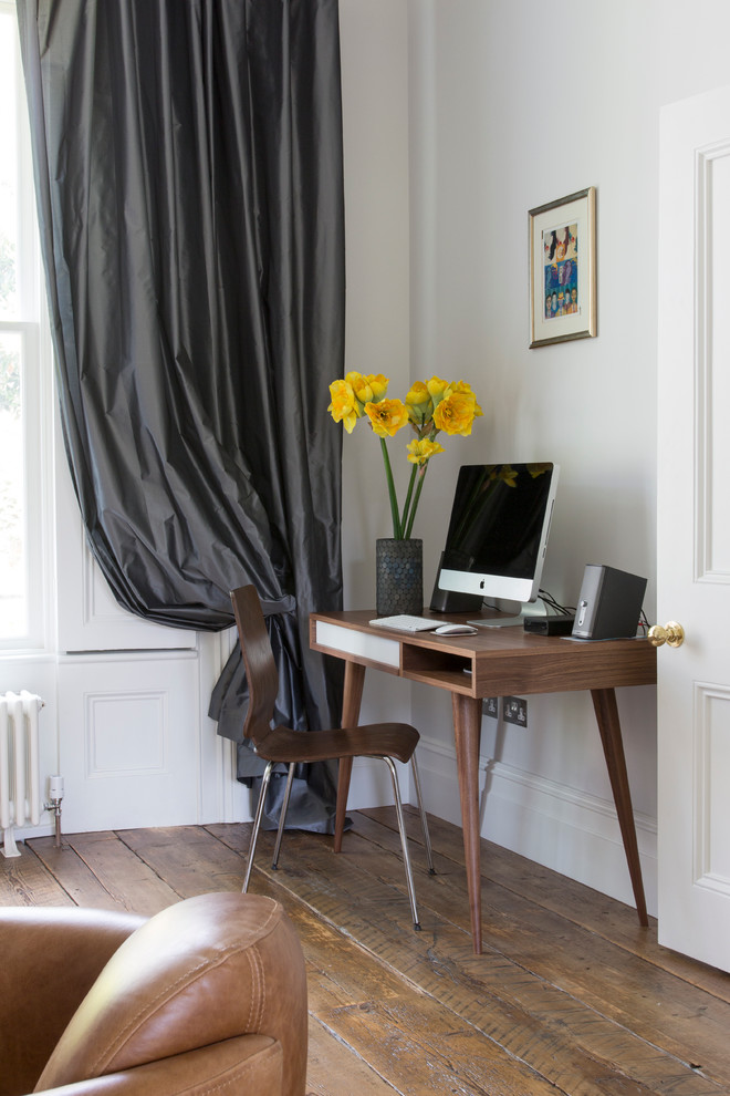 Mid-sized trendy freestanding desk medium tone wood floor home office photo in London with white walls