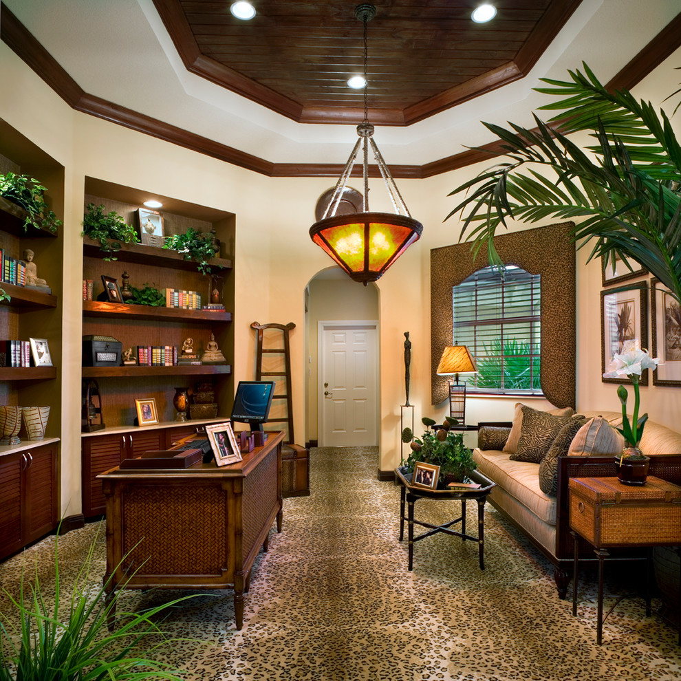 Example of an island style freestanding desk carpeted home office design in Miami with beige walls