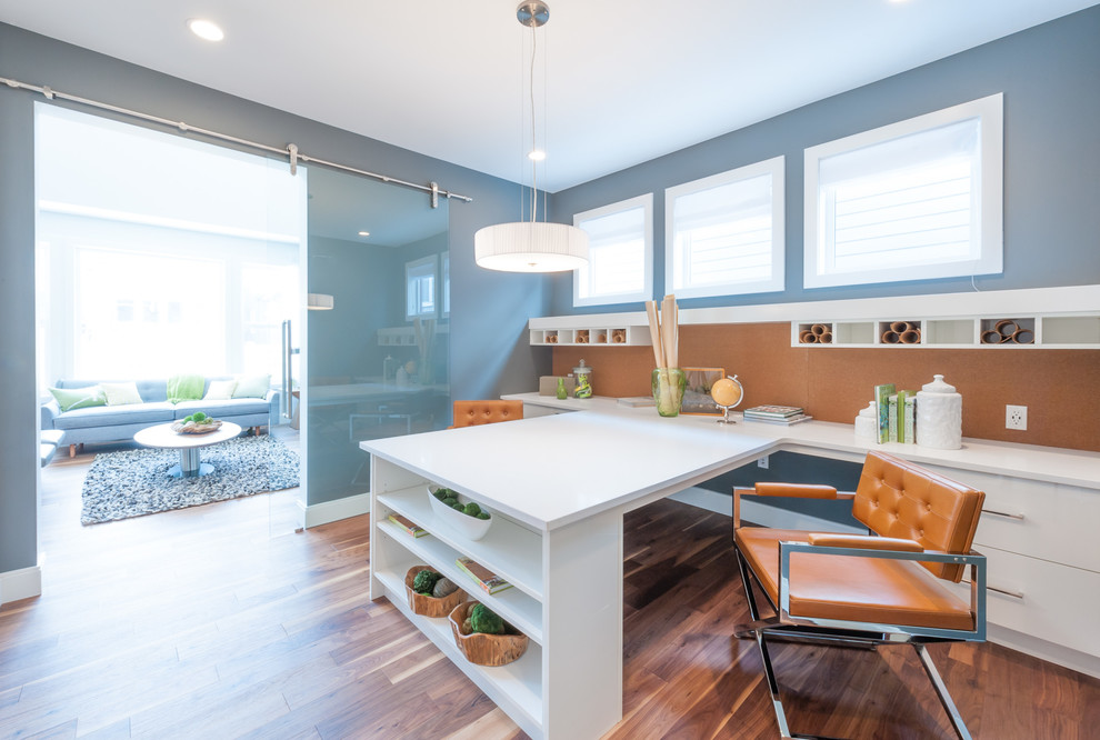 Inspiration for a mid-sized contemporary built-in desk medium tone wood floor and brown floor craft room remodel in Calgary with gray walls