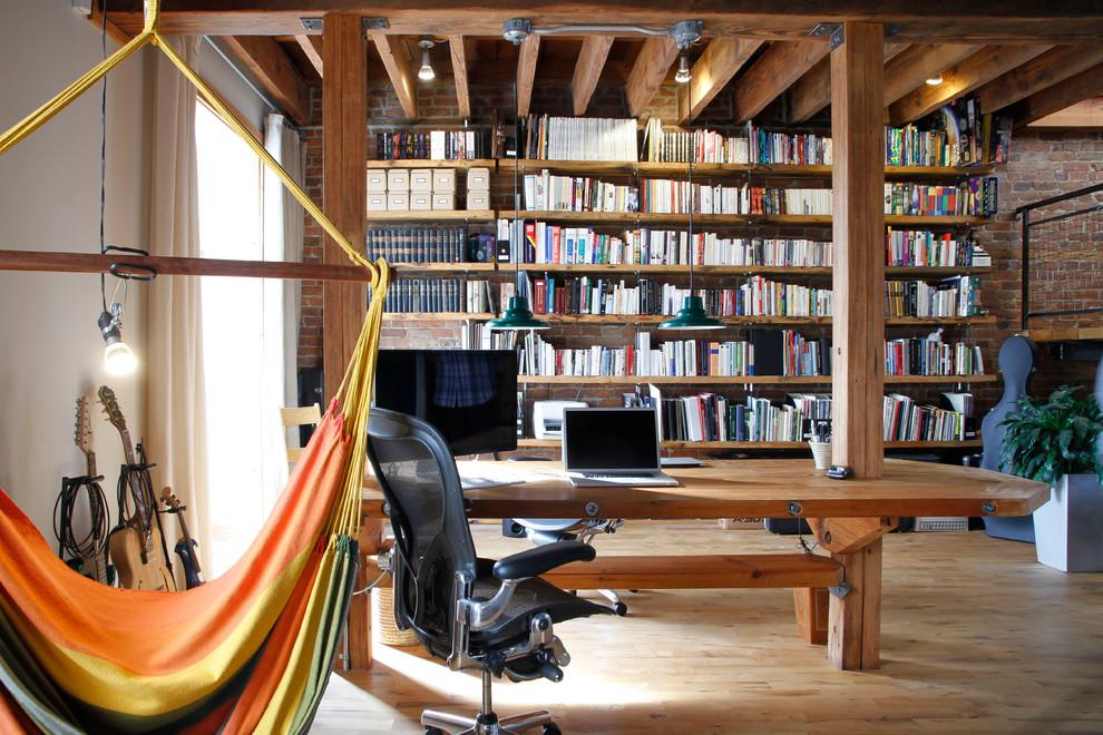 Home office - industrial freestanding desk light wood floor home office idea in Montreal