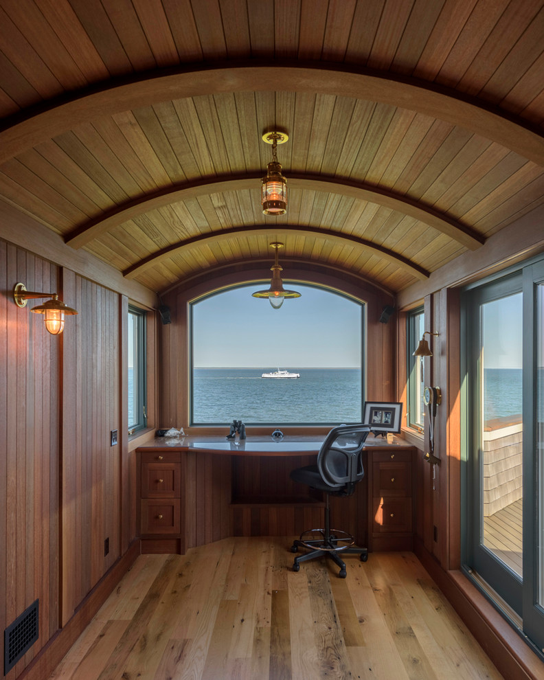 Example of a small beach style built-in desk medium tone wood floor and brown floor study room design in Boston with brown walls and no fireplace