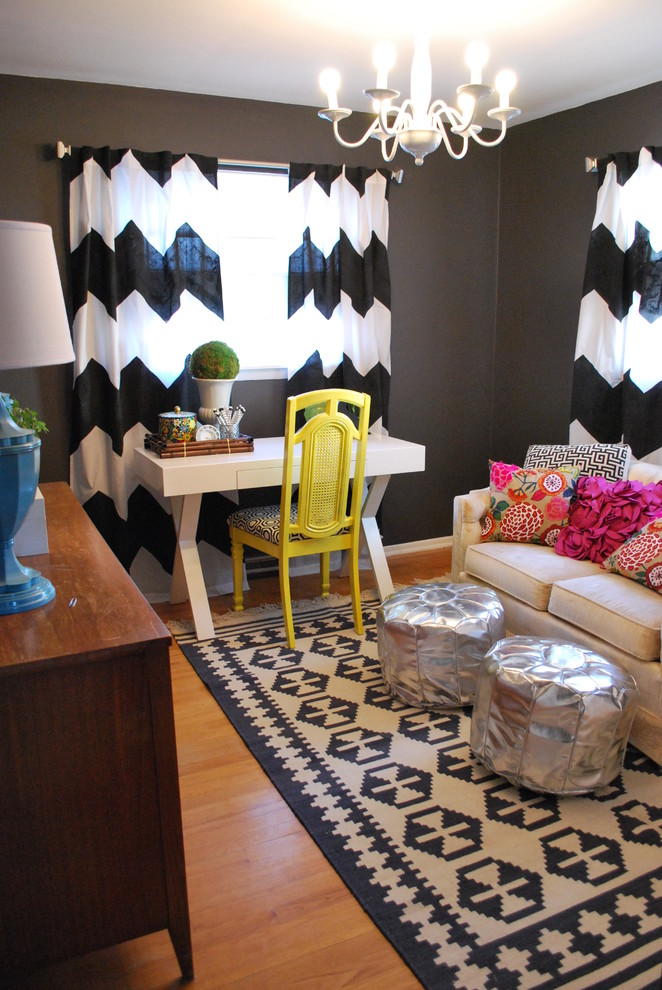 Inspiration for an eclectic freestanding desk medium tone wood floor home office remodel in Other with black walls