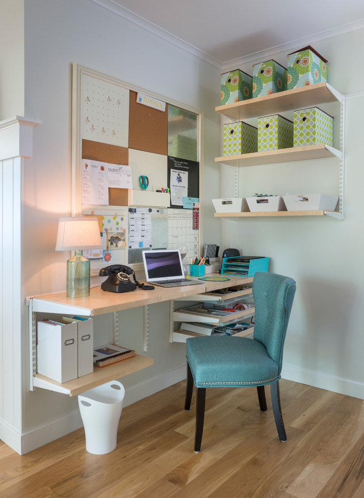 Small cottage built-in desk medium tone wood floor home office photo in Providence with gray walls