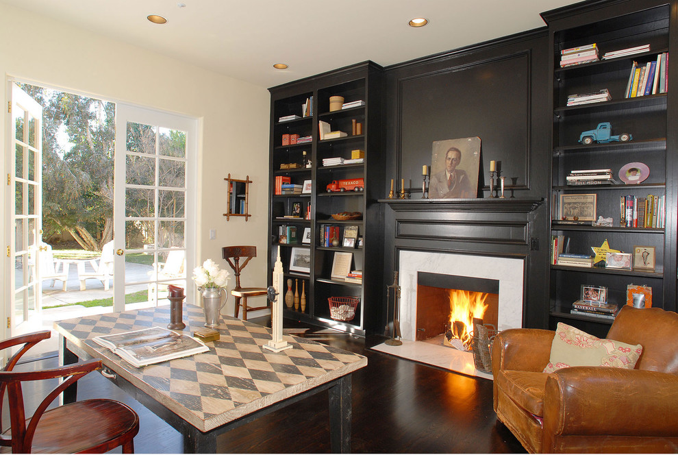 Elegant freestanding desk dark wood floor home office photo in Los Angeles with white walls and a standard fireplace