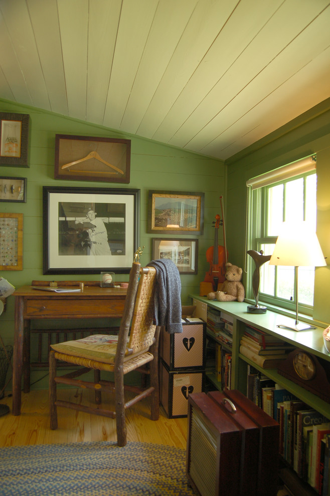 Country freestanding desk medium tone wood floor home office photo in Austin with green walls