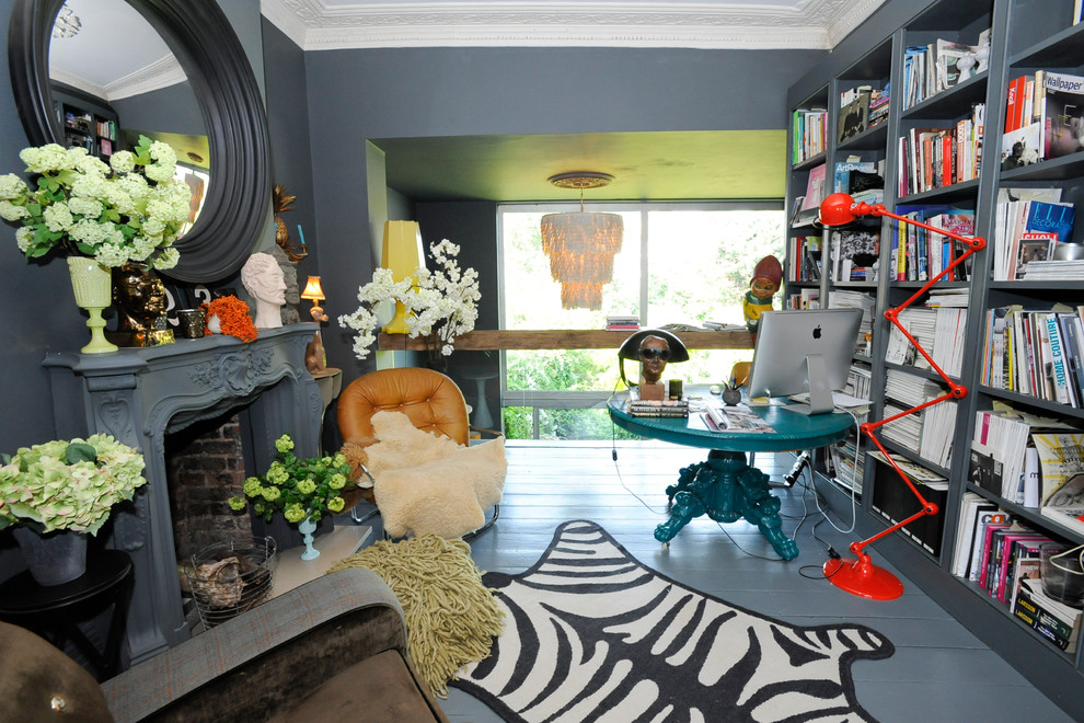 Eclectic freestanding desk painted wood floor and gray floor home office photo in London with gray walls and a standard fireplace