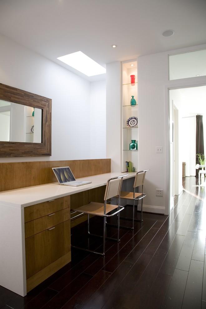 Trendy built-in desk dark wood floor home office photo in DC Metro with white walls