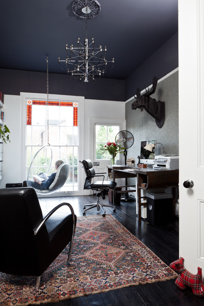Example of a transitional freestanding desk black floor home office design in Birmingham with black walls