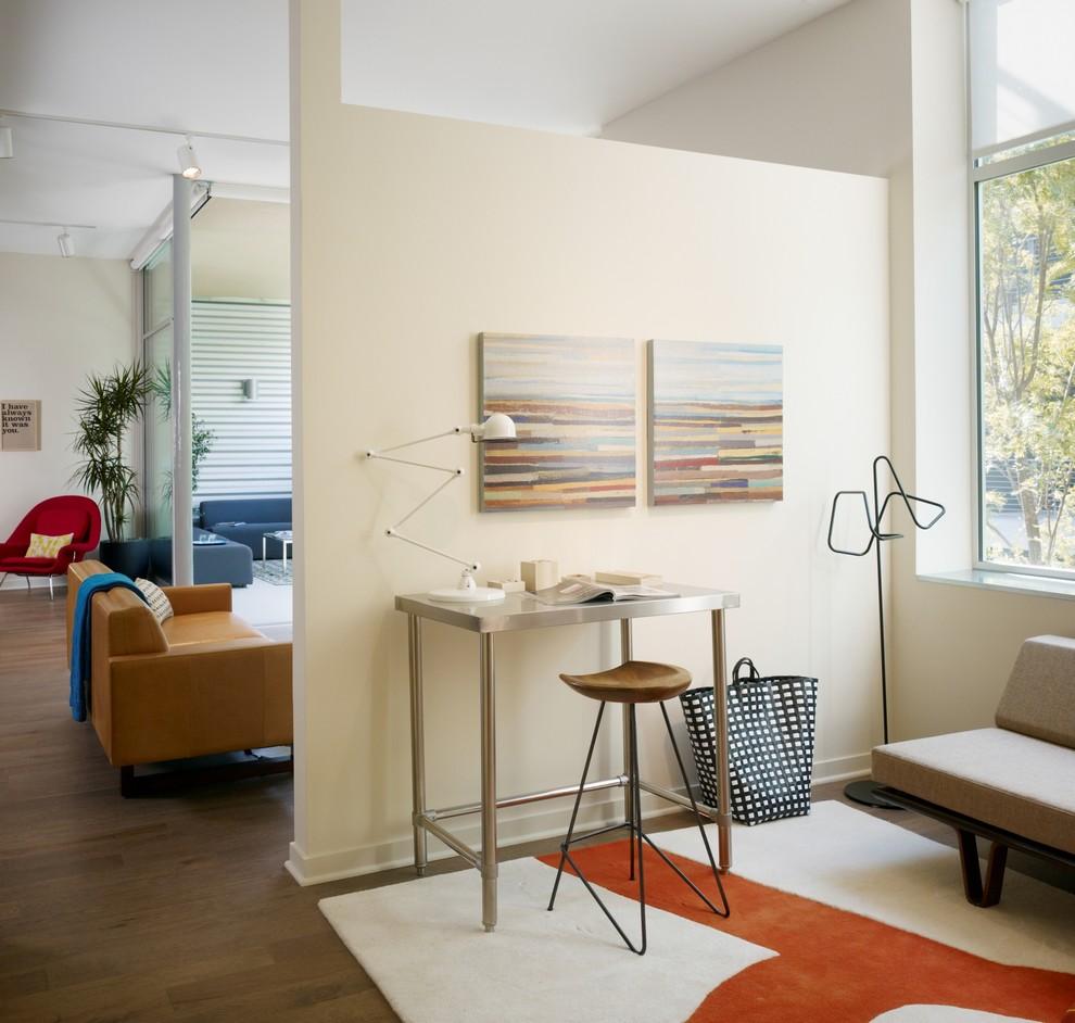 Home office - industrial freestanding desk dark wood floor home office idea in Los Angeles with beige walls