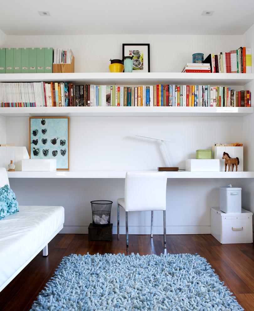 Trendy built-in desk dark wood floor home office photo in Toronto with white walls