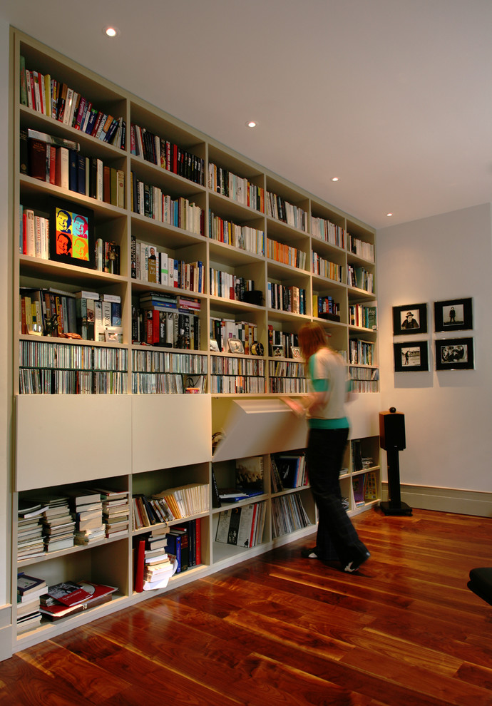 Example of a trendy dark wood floor home office library design in London with white walls