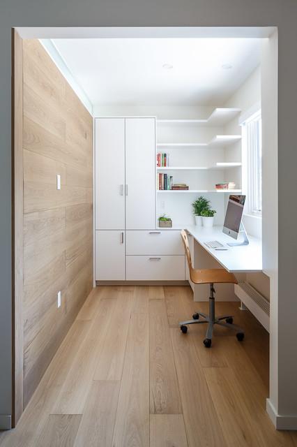 Inredning av ett modernt mellanstort hemmabibliotek, med vita väggar, ljust trägolv, ett inbyggt skrivbord och beiget golv