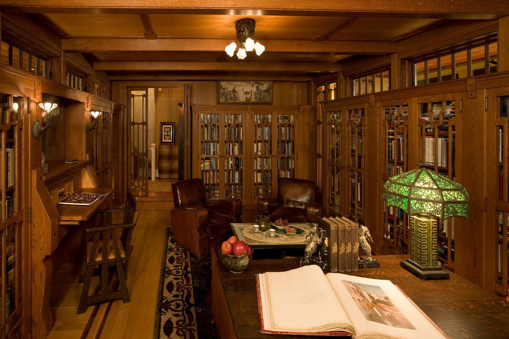 Example of a huge arts and crafts built-in desk dark wood floor study room design in Boston with brown walls and no fireplace