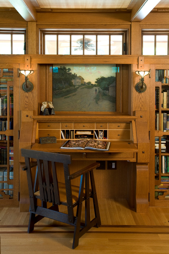 Inspiration for a large craftsman built-in desk medium tone wood floor study room remodel in Boston with brown walls and no fireplace