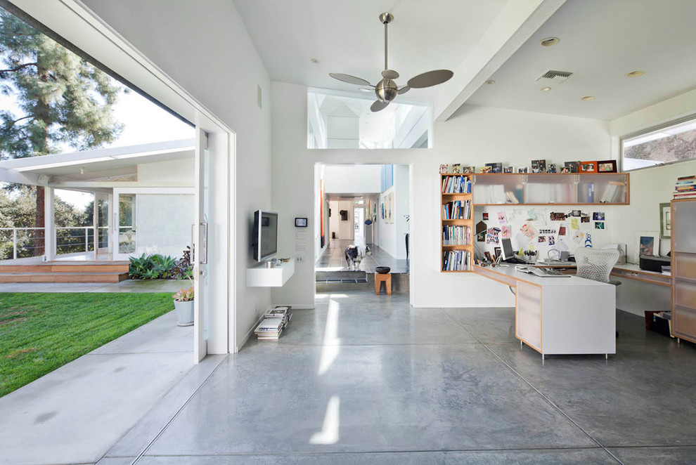 Home office - mid-sized 1950s built-in desk concrete floor and gray floor home office idea in Los Angeles with white walls
