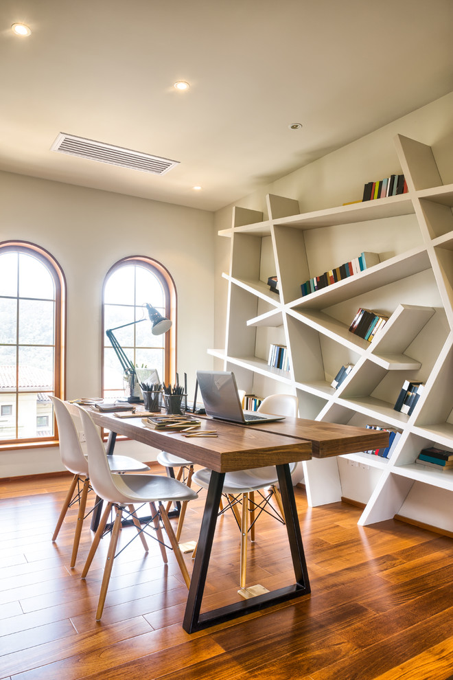 home office with asymmetrical bookshelf and wod floors