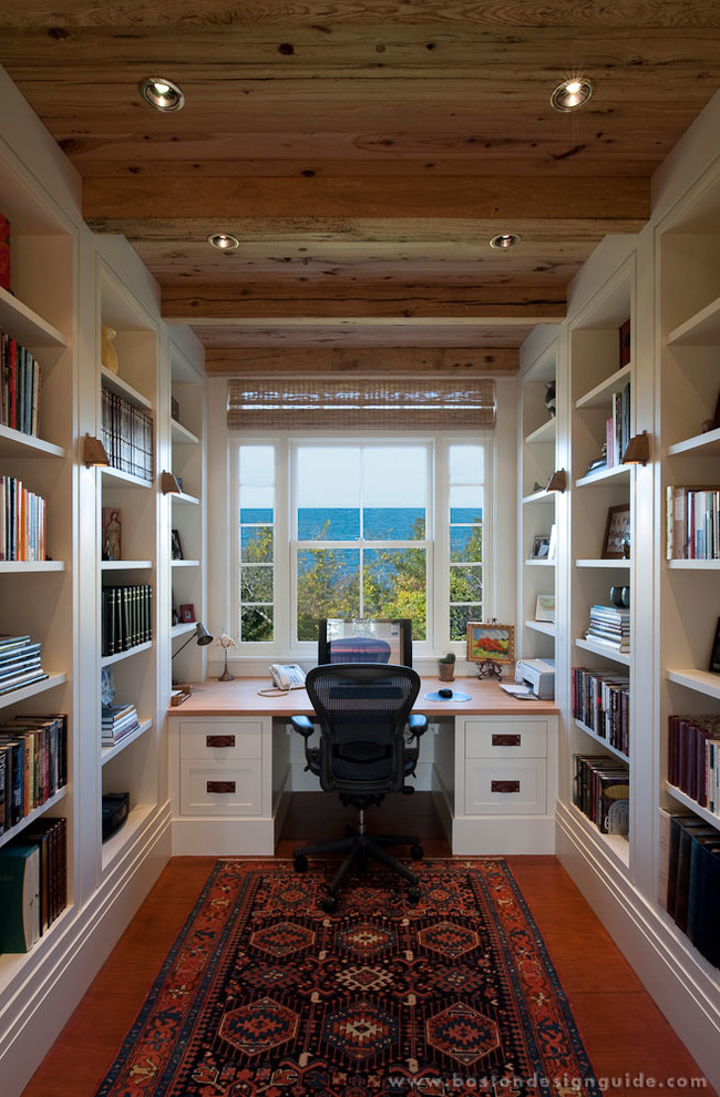 Study room - mid-sized cottage built-in desk medium tone wood floor study room idea in Boston with white walls