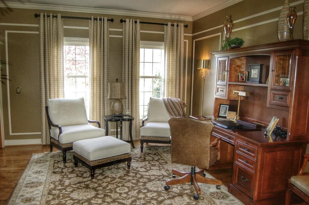 Large elegant freestanding desk medium tone wood floor and brown floor study room photo in Indianapolis with brown walls