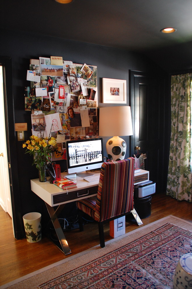Home office - eclectic freestanding desk dark wood floor and brown floor home office idea in Los Angeles with black walls