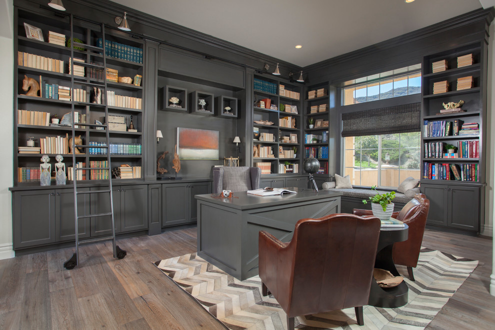 Large elegant freestanding desk dark wood floor home office photo in Orange County with gray walls