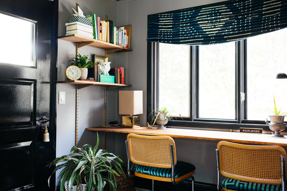 Home office - mid-sized 1960s built-in desk dark wood floor and brown floor home office idea in New York with gray walls and no fireplace