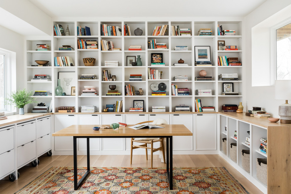 Example of a trendy freestanding desk light wood floor and beige floor home office design in Boston with white walls
