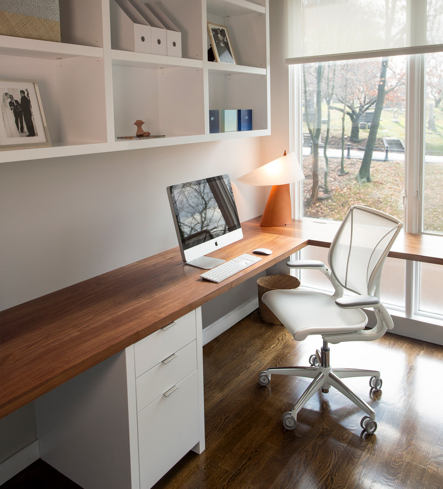 Home office - mid-sized contemporary built-in desk dark wood floor home office idea in New York with white walls