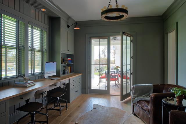 Diseño de despacho de estilo de casa de campo con paredes verdes, suelo de madera clara, escritorio empotrado y suelo marrón
