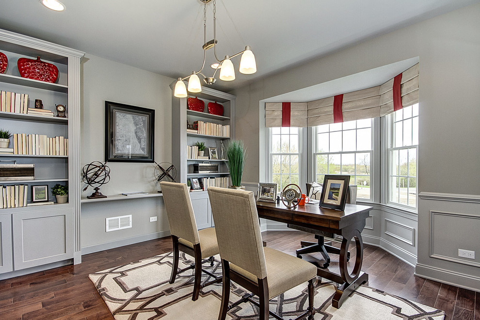 Transitional freestanding desk medium tone wood floor study room photo in Chicago with gray walls