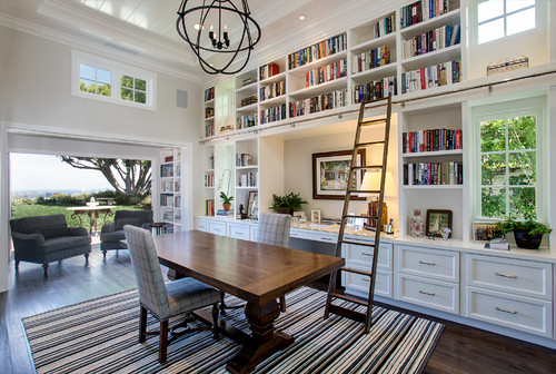 An office with tons of book shelves that could easily be a family room if you put a tv in the large opening in the middle. great storage for books all around.