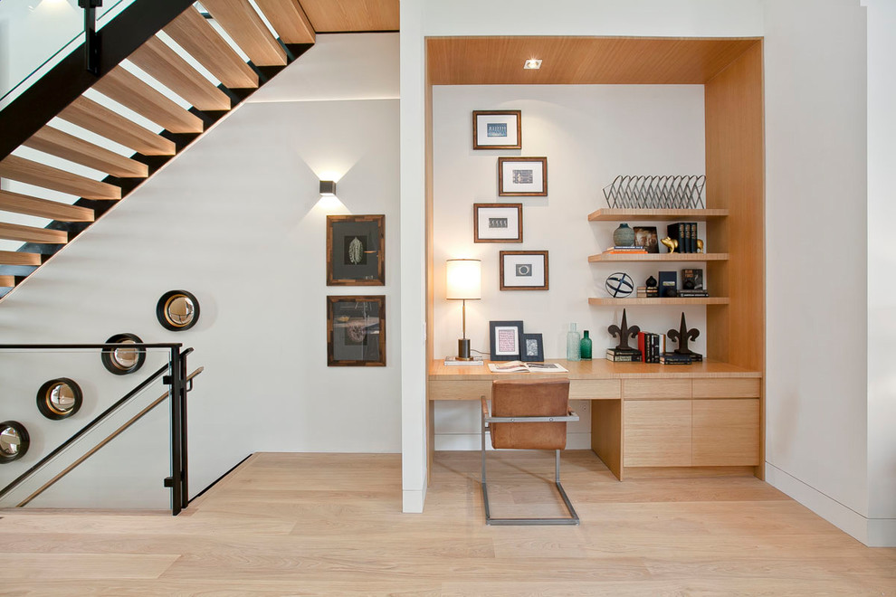 Minimalist built-in desk light wood floor home office photo in San Francisco with white walls